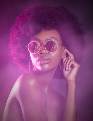 A beautiful black lady looking into the distance wearing sunglasses